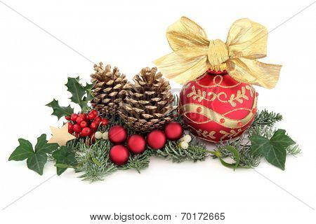 Christmas decoration with holly, red baubles, mistletoe, ivy, fir and cedar leaf sprigs with gold pine cones over white background.