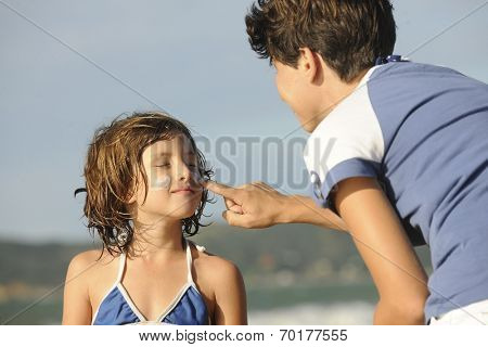 Mother applying sunscreen to daughter at beach