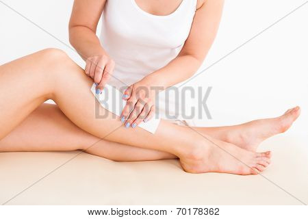 Female Therapist Waxing Customer's Leg