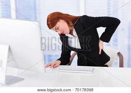 Businesswoman Suffering From Backache At Computer Desk