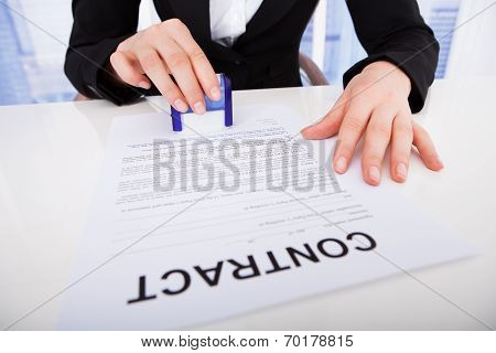 Businesswoman Using Corporate Seal On Contract Paper