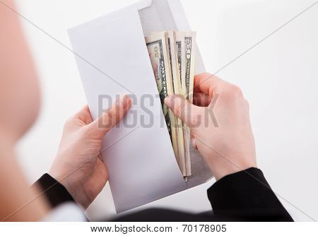 Businesswoman Putting American Banknotes In Envelope