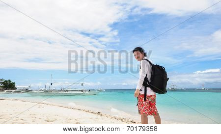happy young man looking back at camera on tropical beach