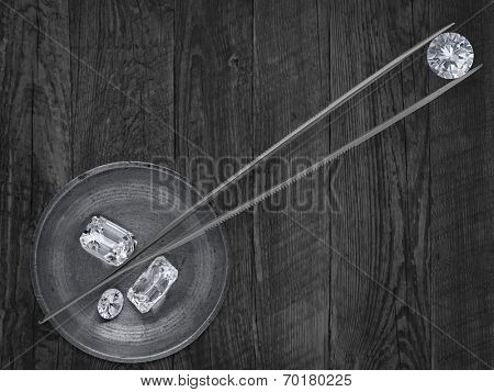 monochromatic image of a various cut cluster of diamonds in a working  brass tray and in tweezers