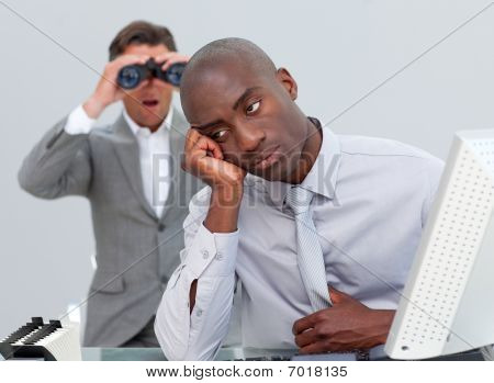 Afro-american Businessman Annoyed By A Man Looking Through Binoculars