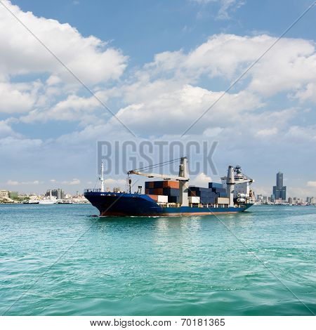 Freighter with cargo sailing on sea with blue sky and green water and beautiful cityscape of buildings and skyscraper in Kaohsiung, Taiwan.