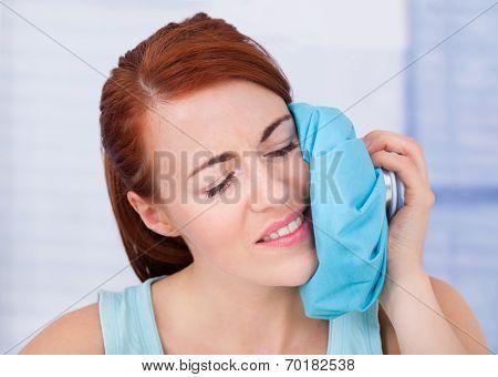 Woman Touching Cheek With Hot Water Bag