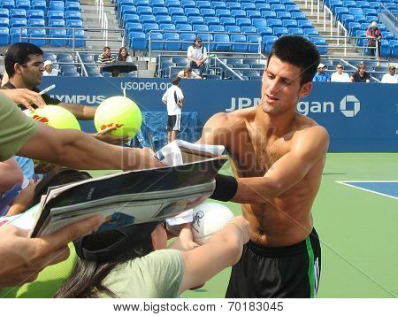 Professional tennis player Novak Djokovic signing autographs after practice