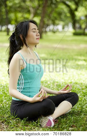 A Beautiful Woman With Earbuds Doing Yoga Meditation Outdoor In A Park