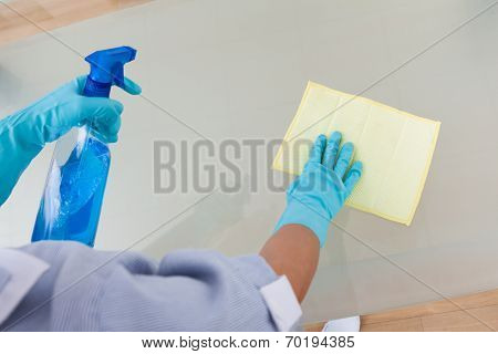 Maid Cleaning Glass Table