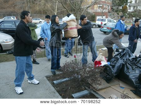 NEW YORK - JANUARY 1:  Sri Lankan-Americans help pass along food and clothing outside the Buddhist Vihara Temple to aid tsunami victims January 1, 2005 in Queens Village, NY.