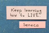 picture of interpreter  - famous ancient Roman philosopher Seneca quote interpretation with sticky notes on vintage carton board about keep learning - JPG