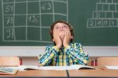 stock photo of boredom  - Young schoolboy searching for answers sitting at his desk in the classroom staring up into the air with a thoughtful expression - JPG