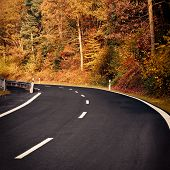 image of curvy  - Curvy country road in autumn leading through a mountain landscape - JPG