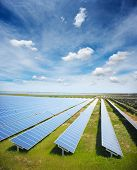 picture of solar battery  - Solar panels with green field and cloudy sky - JPG