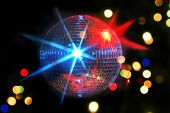image of laser beam  - Disco or mirror ball with different colored laser beam lights shining on black background - JPG