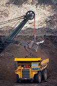 image of earth-mover  - Yellow big mining truck unload coal - JPG