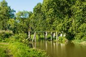 picture of neglect  - Neglected drawbridge over a narrow stream overgrown with bushes and plants - JPG
