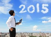 image of new year 2014  - Young business man using laptop and look to 2015 year text with blue sky and cloud and cityscape in the background asian - JPG