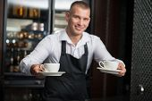 stock photo of apron  - Selective focus on two white cups in the hands of handsome young smiling barista wearing white shirt and black apron suggested us to taste his coffee on background