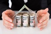 picture of crop  - Cropped image of businesswoman protecting house made of dollar bills at office desk - JPG