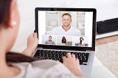 image of video chat  - Cropped image of young woman using laptop for video conference at home - JPG