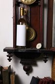 foto of pendulum clock  - Bottle of white wine with blank label template standing inside an old clock - JPG