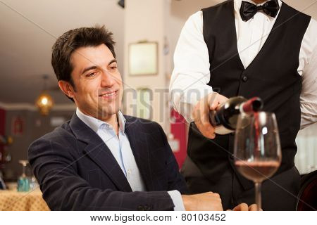 Waiter pouring wine in a glass