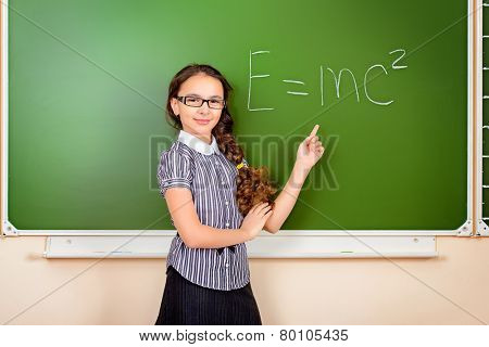 A schoolgirl in spectacles stands at the blackboard during a physics lesson. Education.
