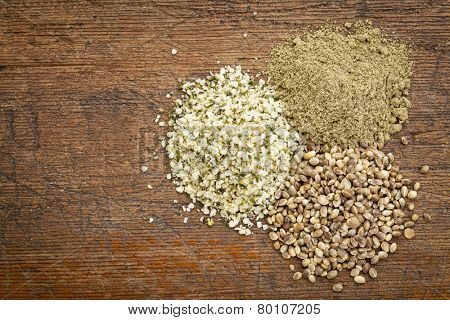hemp seed, hearts and protein powder - small piles on a grunge wood - top view
