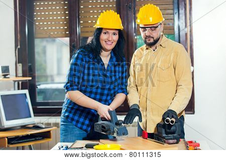 Home improvement - handy woman sanding wooden floor in workshop, handy man assisting