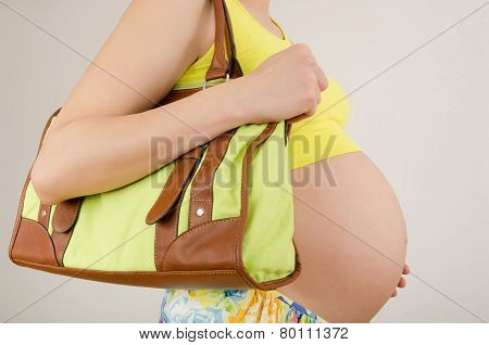 Woman expecting a baby holding a bag in her hands.