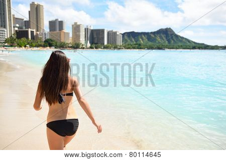 Bikini woman on Waikiki Beach, Oahu, Hawaii, USA. Girl on travel vacation holidays running having fun on Hawaiian Waikiki beach with Diamond Head mountain. Rear back view of girl walking away.