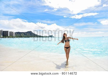 Happy beach woman in bikini joyful and free on Waikiki, Oahu, Hawaii, USA. Girl on travel vacation holidays having fun on Hawaiian Waikiki beach with Diamond Head mountain. Asian Caucasian model.