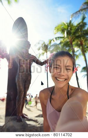 Waikiki Beach Tourist in Honolulu on Oahu, Hawaii taking selfie self portrait photograph in front of famous tourist attraction and surfing landmark, the statue of Duke Kahanamoku. Travel on Hawaii.