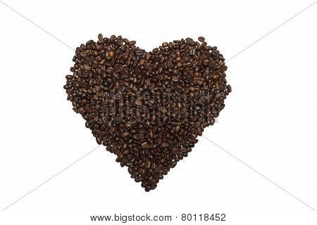 Heart laid out by of roasted coffee beans.