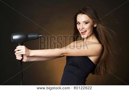 Beautiful young woman with long hair holding hair dryer on dark brown background