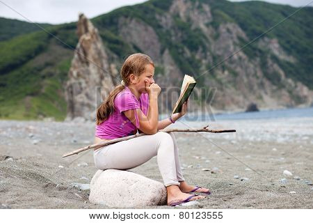 Girl Reading Book Sitting On A Stone On A Sandy Sea Shore