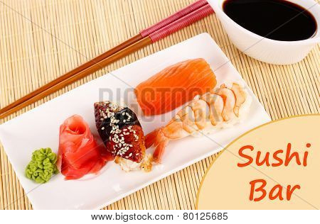 Delicious sushi served on plate on bamboo mat with space for your text