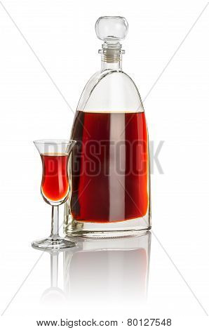 Carafe and high stem glass filled with brown liquid