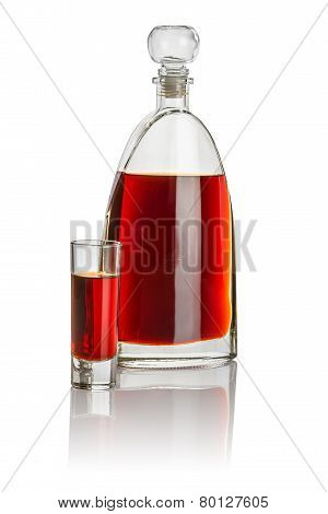 Carafe and high shot glass filled with brown liquid