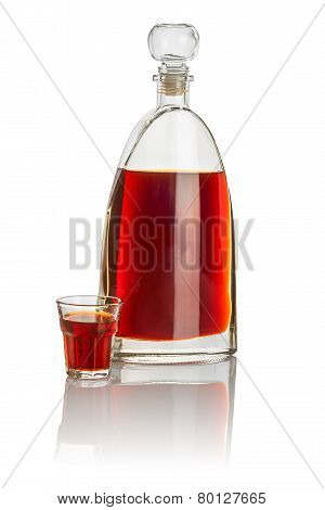 Carafe and beveled shot glass filled with brown liquid