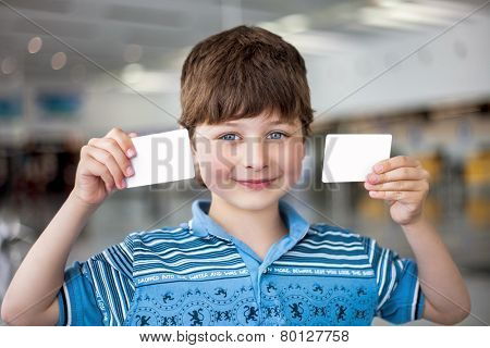 Portrait of smiling boy with two cards in the hands