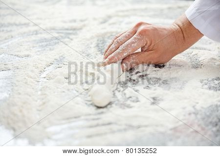 Cropped image of female chef's hand holding dough at messy counter in commercial kitchen