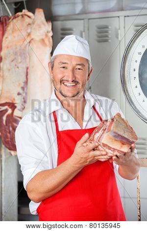 Portrait of happy butcher holding meat in shop