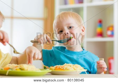kid boy eating spaghetti in nursery