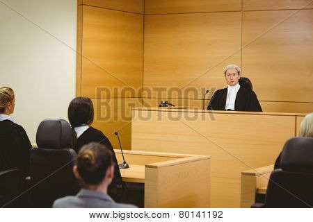 Unsmiling judge wearing wig with american flag behind him in the court room