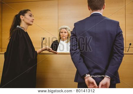 Lawyer talking with the criminal in handcuffs in the court room