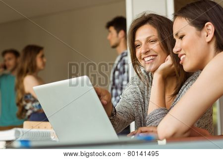 Smiling friends sitting using laptop near classmates at school