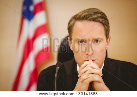 Portrait of a serious judge with american flag behind him in the court room